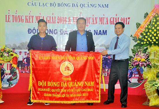 Phó Chủ tịch UBND tỉnh Lê Văn Thanh tặng cờ của UBND tỉnh cho đội bóng Quảng Nam.Ảnh: T.VY
