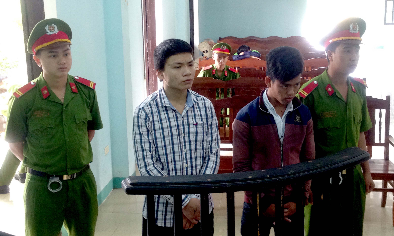 Bị cáo Nguyễn Quốc Hùng (áo sọc trắng) và bị cáo Đỗ Vũ (áo đen đà) trước vành móng ngựa. Ảnh: VINH CHÂU
