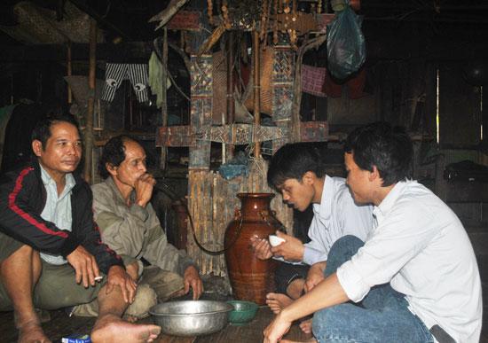 Già làng Hồ Văn Chính cùng con cháu và bà con vui bên ché rượu cần trong tết máng nước đầu năm của gia đình mình. Ảnh: N.V.S