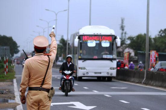 Cán bộ trạm CSGT Thăng Bình kiểm tra xe khách trên tuyến quốc lộ 1 vào sáng ngày 5.2.Ảnh: THÀNH CÔNG