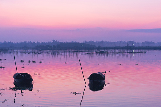 Bắt đầu một ngày mới trên bến sông, ráng hồng xa xa cuối chân trời, một con đò ngang cắm sào nằm đợi cũng đủ làm nao lòng lữ khách.