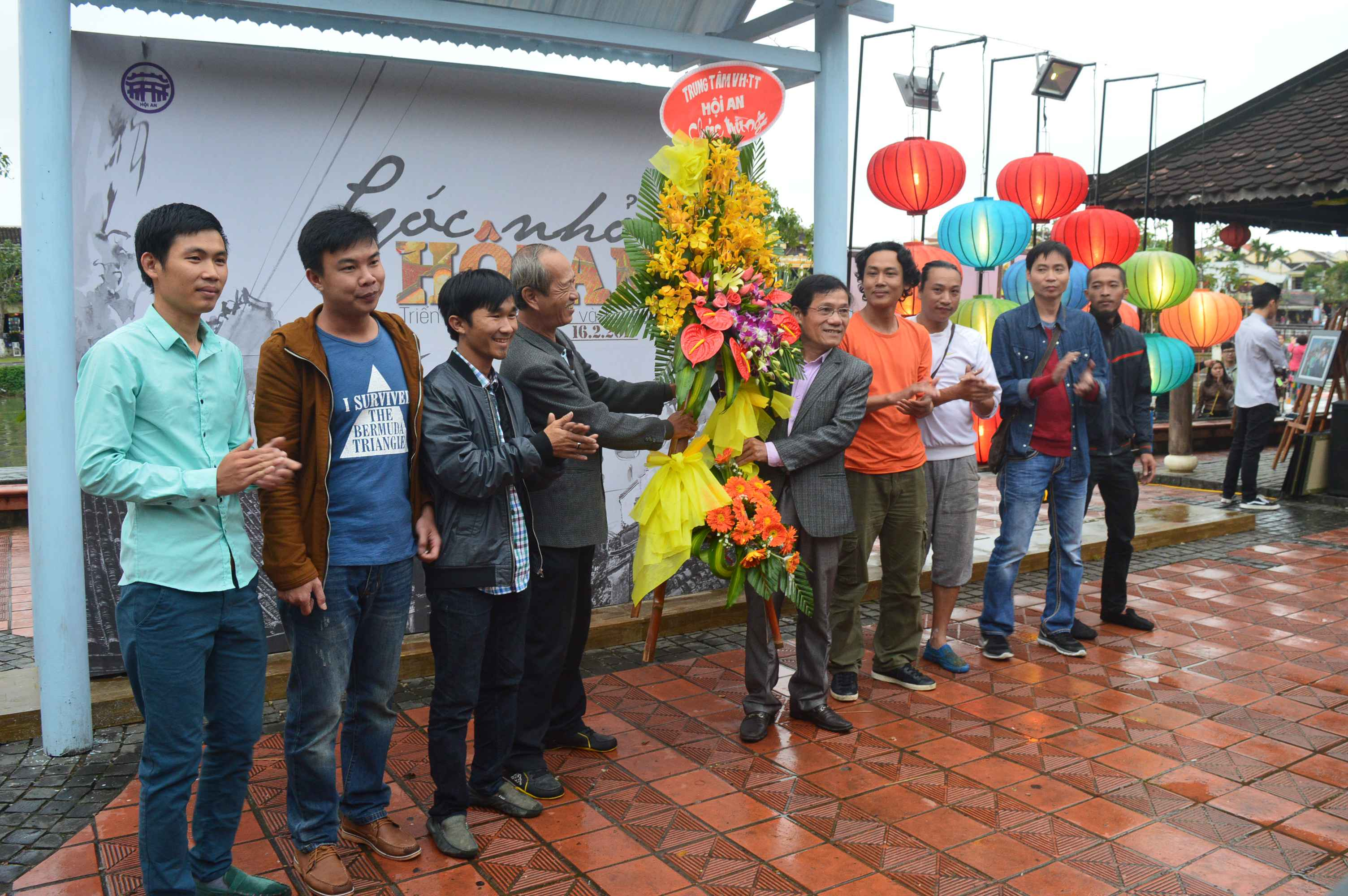 Phó trưởng phòng VH-TT Hội An tặng hoa chúc mừng các nghệ sĩ có tác phẩm trong triển lãm. Ảnh: Q.T