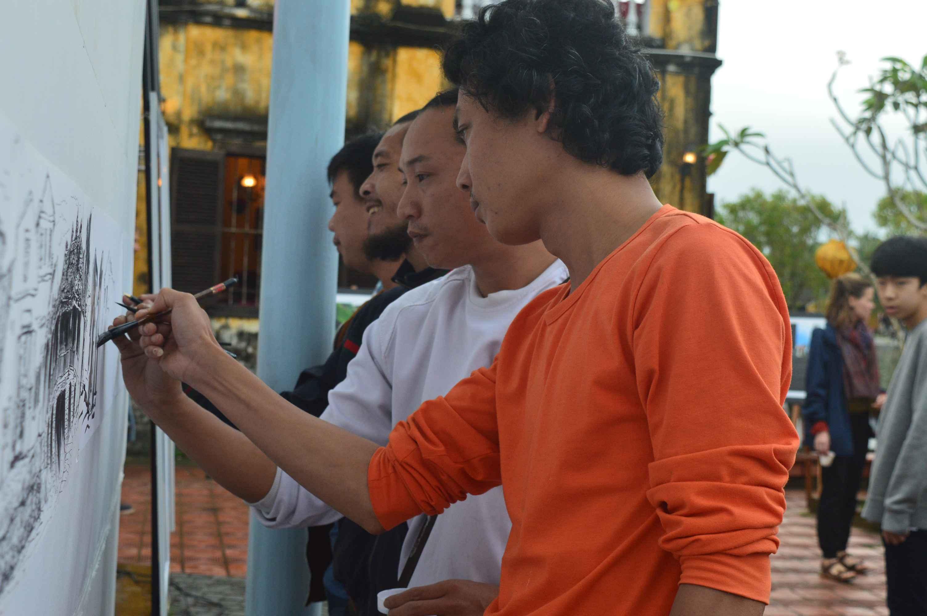 Các họa sĩ tiếp tục vẽ bức tranh về phố phường Hội An sau lễ khai mạc. Ảnh: Q.T
