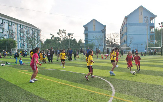 Các em học sinh thi đấu trên sân cỏ nhân tạo. Ảnh: L.T
