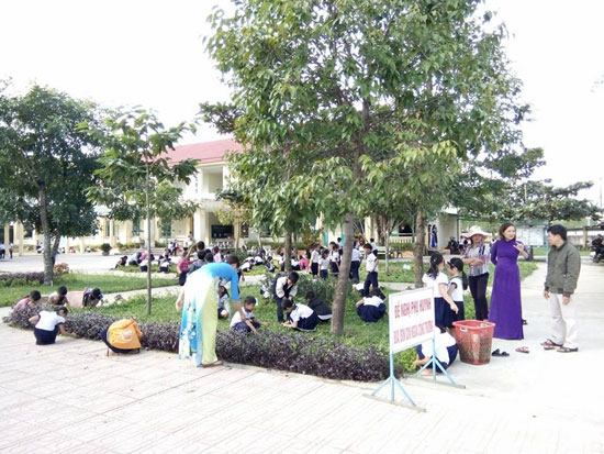 Giáo viên và học sinh Trường Tiểu học Ngô Quyền chăm sóc khuôn viên nhà trường. Ảnh CHÂU NỮ