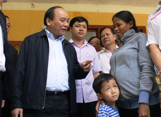 Chị Hồ Thị Hiếu nhận lời động viên của đồng chí Nguyễn Xuân Phúc, vào tháng 3.2016, lúc bấy giờ là Phó Thủ tướng Chính phủ. Ảnh: N.T