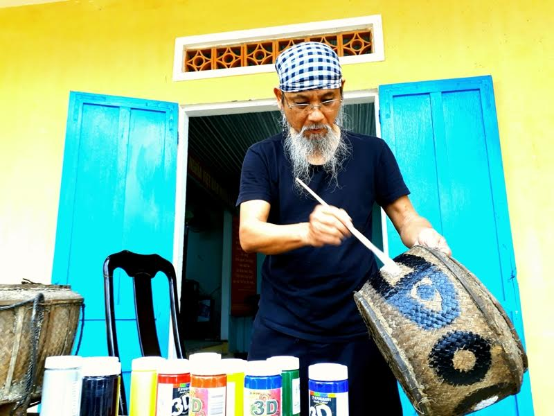 Họa sỹ Phan Cẩm Thượng (đến từ Hà Nội) thực hiện tác phẩm của mình trên các vật dụng thường ngày của người dân xã biển Tam Thanh.