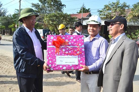 Chủ tịch Đinh Văn Thu tặng quà động viên nhà thầu thi công đường vào trung tâm du lịch phố cổ. Ảnh: CÔNG TÚ