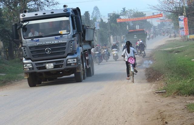 Xe tải chở cát nuối đuôi nhau trên tỉnh lộ. Ảnh: TRIÊU NHAN