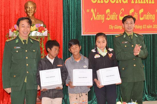 Cán bộ, chiến sĩ Đồn Biên phòng A Xan (Tây Giang) trao quà hỗ trợ  nhận đỡ đầu các em học sinh khó khăn. Ảnh: Đ.N
