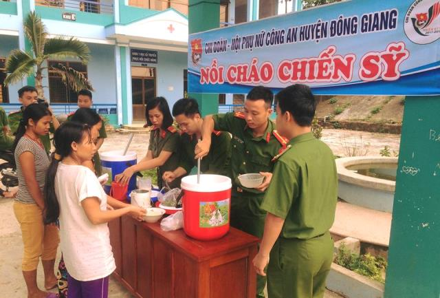 Các chiến sĩ công an huyện trao những bát cháo nóng hổi cho bệnh nhân. Ảnh: ML