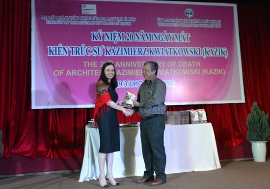 Ms. Barbara Szymaowska offers a book about Kazik to Secretary of the Hoi An city Party Committee Kieu Cu.