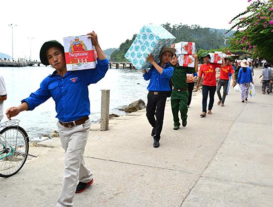 Đoàn viên thanh niên mang hàng ra Cù Lao Chàm trong một chuyến tình nguyện.  Ảnh: VINH ANH