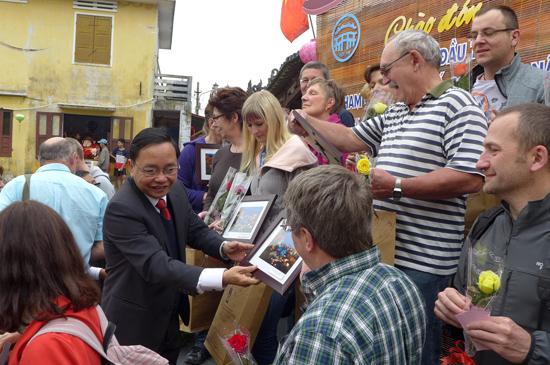 Ông Đinh Hài - Giám đốc Sở VH-TT&DL tặng quà lưu niệm cho du khách tại Hội An.