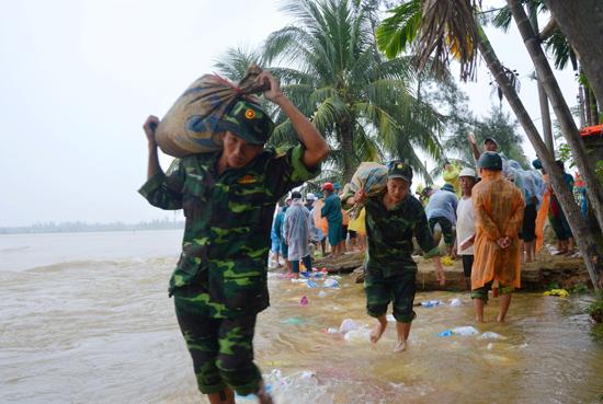 Cán bộ, chiến sĩ thuộc Bộ CHQS tỉnh tham gia đắp kè bờ biển, ứng phó với bão lũ.