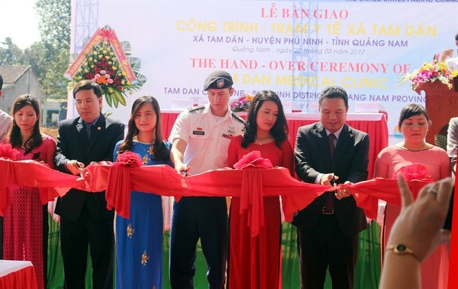 Representatives of both parties cut ribbons in the hand-over ceremony