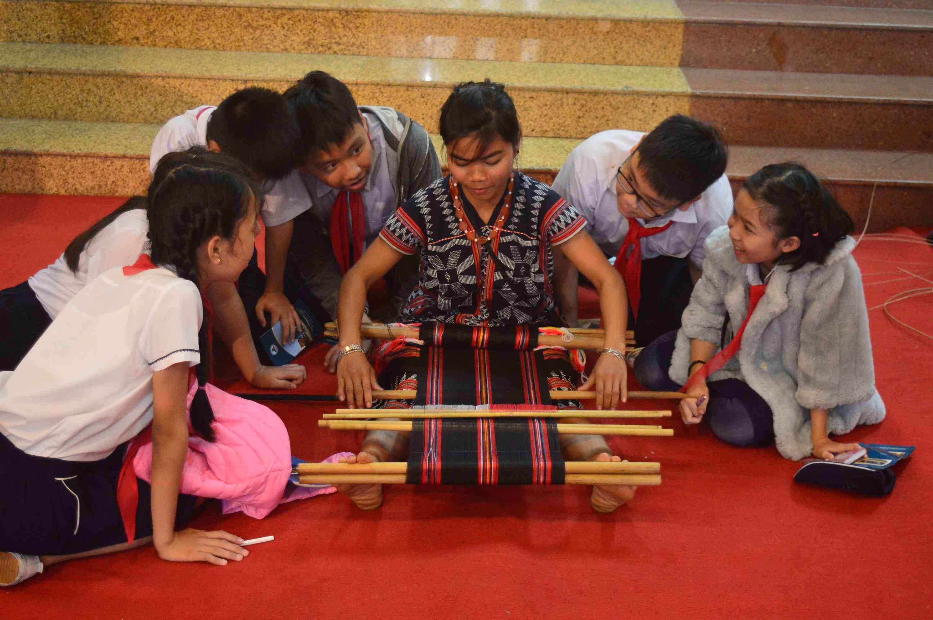 Học sinh hào hứng xem biểu diễn nghề dệt truyền thống của đồng bào Cơ tu huyện Đông Giang. Ảnh: Q.T