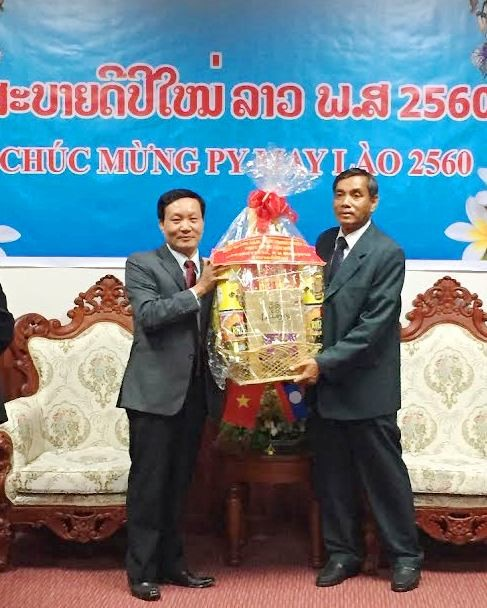 Vice Chairman Tran Dinh Tung (left) congratulates Lao traditional New Year