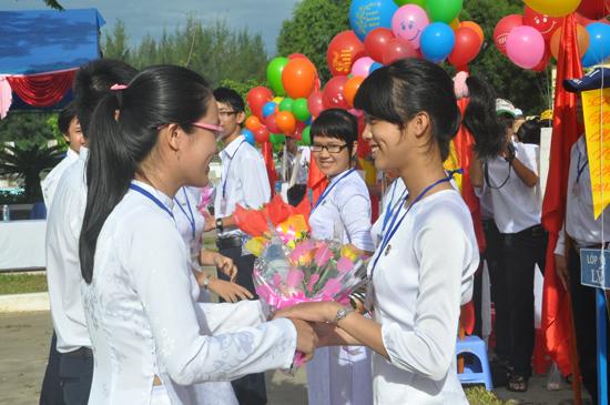 Học sinh lớp 12 tặng hoa chúc mừng học sinh lớp 10 vừa trúng tuyển vào trường tại lễ khai giảng năm học mới của Trường THPT chuyên Nguyễn Bỉnh Khiêm. Ảnh: XUÂN PHÚ