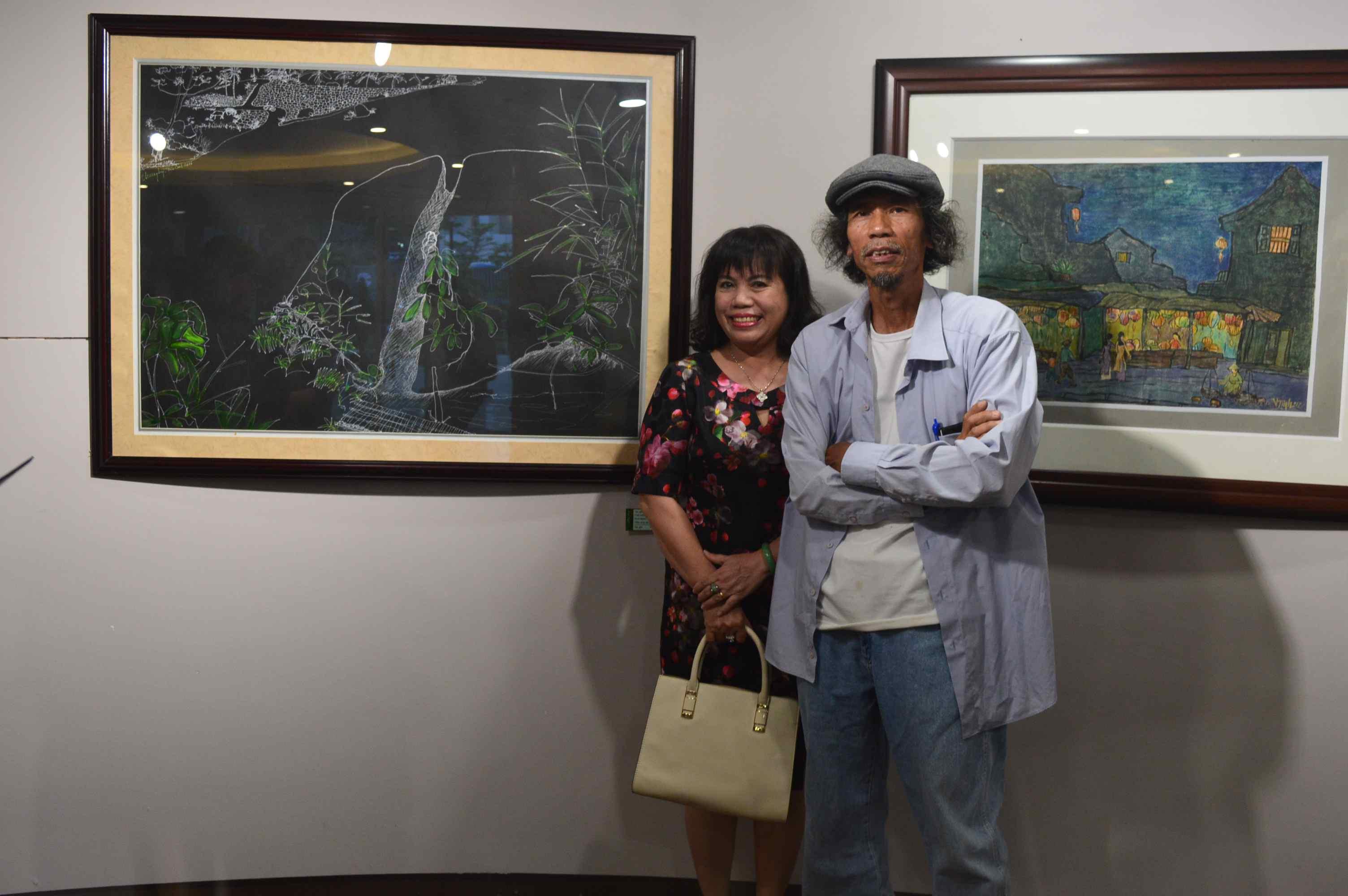Họa sỹ Nguyễn Thượng Hỷ (phải) bên tác phẩm của mình trưng bày tại triển lãm. Ảnh: Q.T
