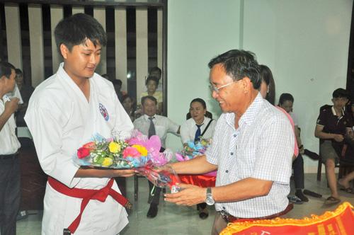 Giám đốc Sở VH-TT&DL Đinh Hài tặng hoa động viên các vận động viên tại lễ khai mạc. Ảnh: T.VY