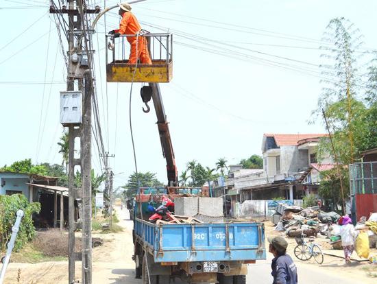 Công nhân nhà thầu xây lắp điện chuẩn bị di dời hệ thống điện ra khỏi phạm vi dự án. Ảnh: C.T