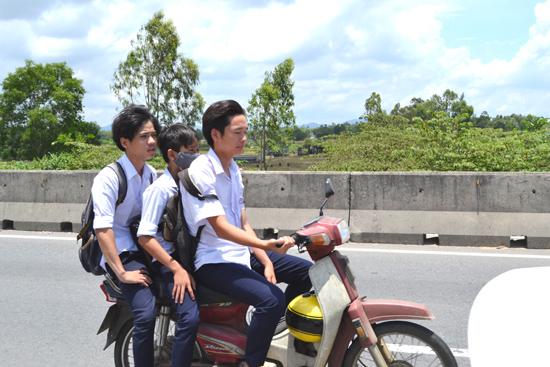 Học sinh đi xe máy chở ba, không đội mũ bảo hiểm diễn ra trên quốc lộ 1. Ảnh: S.C
