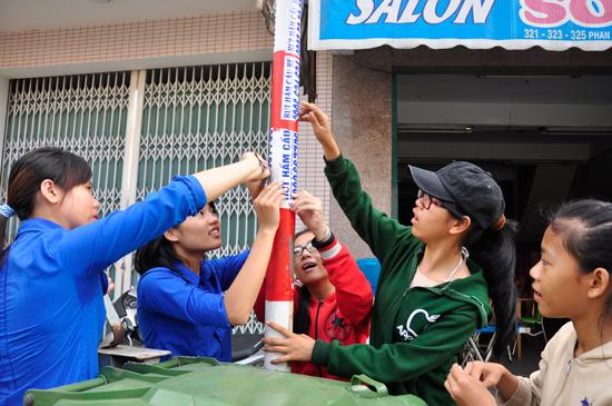 Đoàn viên thanh niên bóc, xé quảng cáo trên các tuyến đường TP.Tam Kỳ. Ảnh: VINH ANH