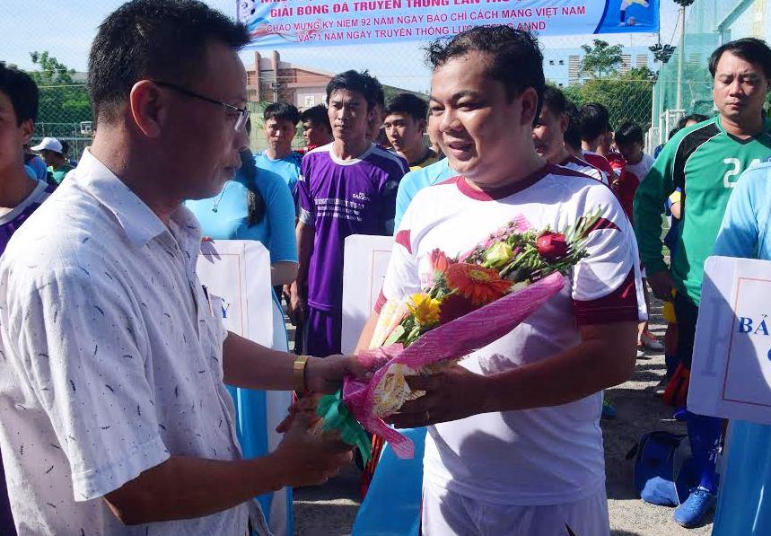 Ông Lê Văn Nhi – Tổng Biên tập báo Quảng Nam tặng cờ và hoa cho các đội tham gia. THANH THẮNG.