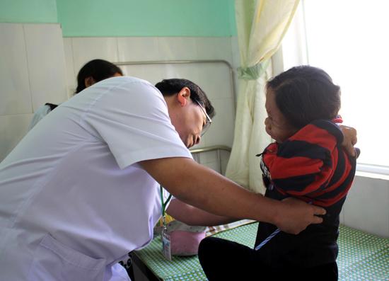 Bác sĩ Tơ Ngôl Vui đang khám và điều trị cho một bệnh nhân nước bạn Lào. Ảnh: N.T