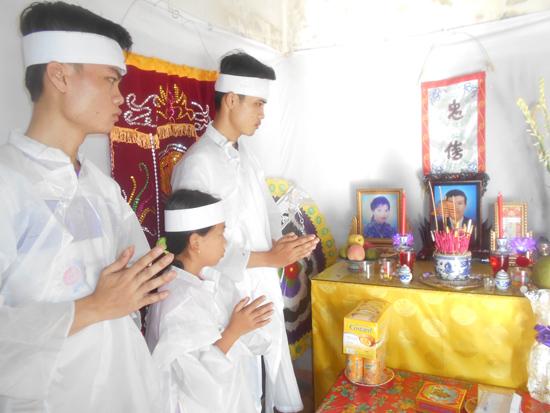 3 cháu trước bàn thờ của cha mẹ. Ảnh: H.H
