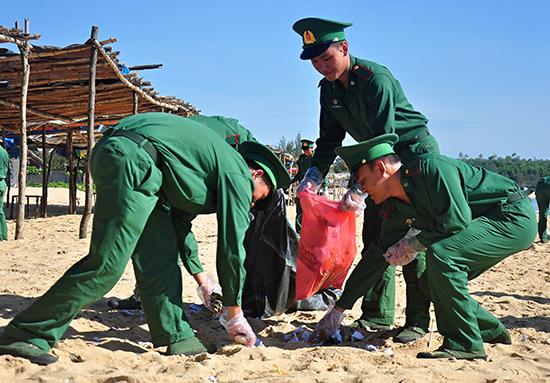 Các chiến sĩ Bộ đội Biên phòng hưởng ứng hoạt động làm sạch bãi biển xã Tam Quang sau lễ ra quân chiến dịch Thanh niên tình nguyện hè 2017. Ảnh: VINH ANH