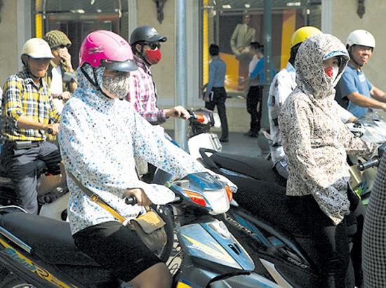 Khi nắng nóng cần uống nhiều nước,  mặc quần áo rộng, nhẹ và sáng màu, đội mũ kết hợp với sử dụng kem chống nắng để phòng tránh say nắng.      Ảnh: TM