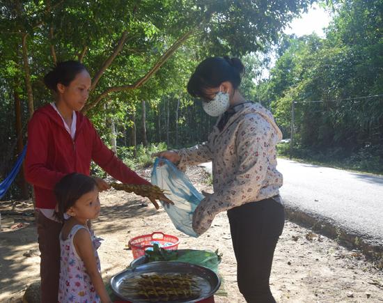 Chị Bông (bìa trái) đang bán cá bống đã được nướng thơm lừng cho du khách. Ảnh: THẮNG DƯƠNG