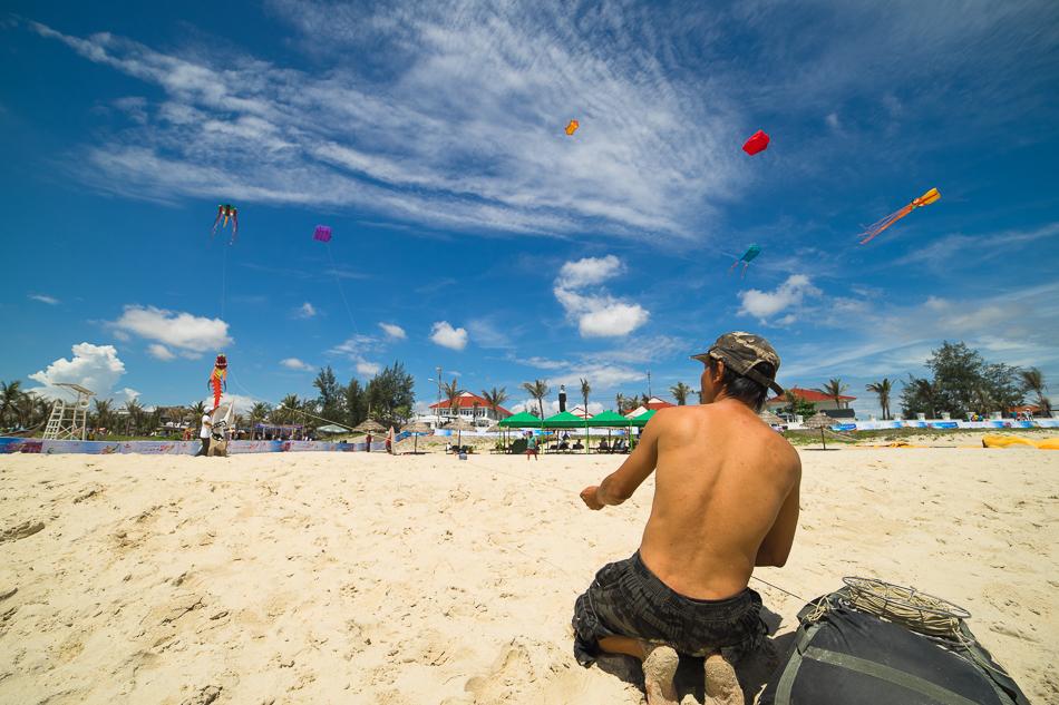 Trân mình dưới nắng, một nghệ nhận điều khiểu diều trên bãi biển Tam Thanh. Ảnh: HÀ NGUYỄN