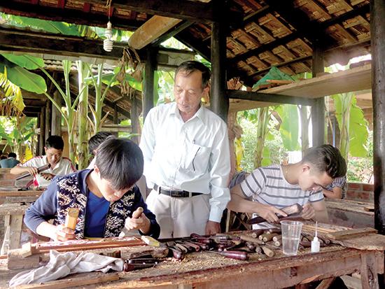 Nghệ nhân nhân dân Nguyễn Văn Tiếp vẫn bền bỉ truyền nghề cho các thế hệ người làng Điện Phương. Ảnh: LÊ QUÂN