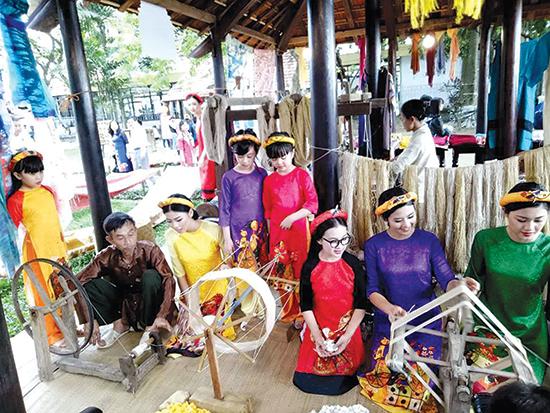 nhiều người hào hứng khi được tham gia vào các công đoạn trình diễn dệt lụa Mã Châu tại Làng Lụa Hội An.