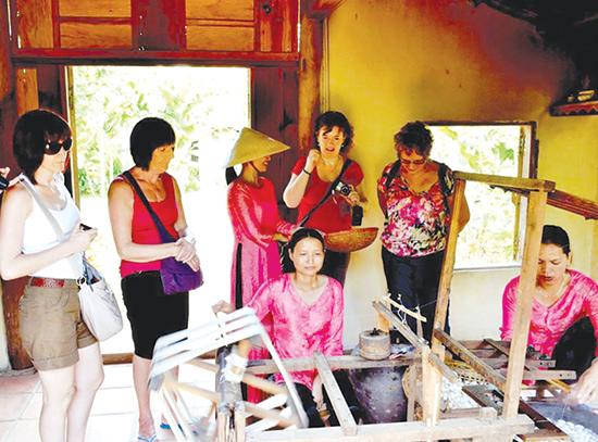 Du khách nước ngoài tham quan kỹ thuật dệt lụa Mã Châu tại Làng Lụa Hội An.