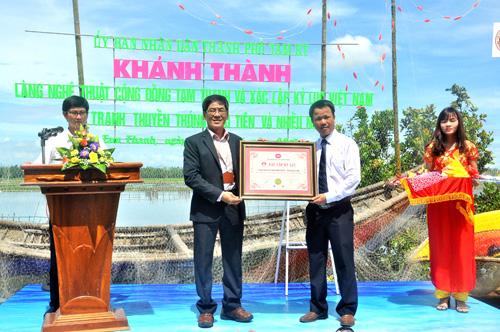 Đại diện Tổ chức kỷ lục Việt Nam trao bằng xác nhận kỷ lục Việt Nam cho bộ tranh thuyền thúng Tam Thanh. Ảnh: X.PHÚ