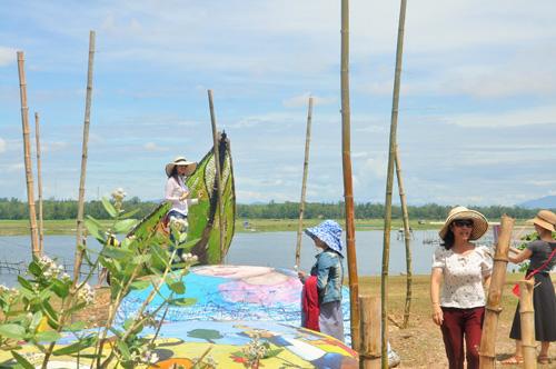 Nhiều du khách tham quan, chụp ảnh lưu niệm tại khu vực tranh thuyền thúng. Ảnh: X.PHÚ