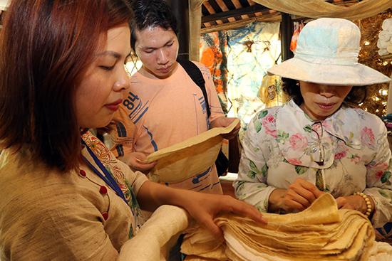 Du khách tìm hiểu chất lượng tơ lụa tại một gian trưng bày. Ảnh: THÀNH CÔNG