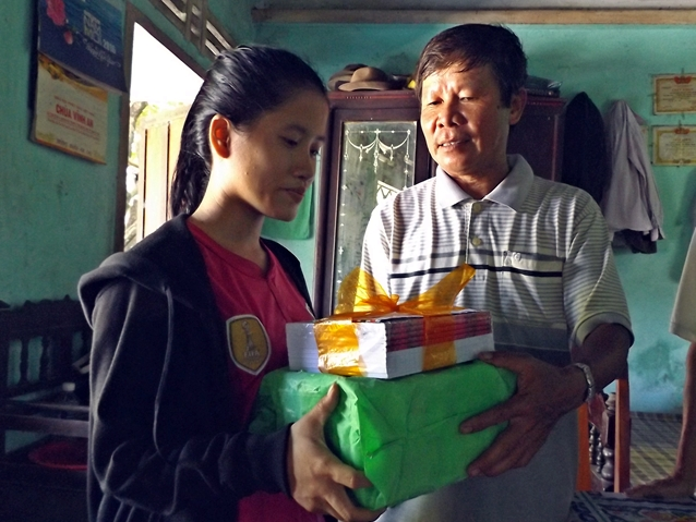 Chi bộ thôn Bà Bầu học Bác làm những việc có ích cho nhân dân địa phương. (Trong ảnh: Đại diện Chi bộ thôn Bà Bầu tặng quà cho em Trương Thị Thanh Tuyền). Ảnh: ĐOÀN ĐẠO