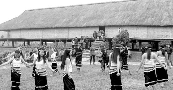 Các thiếu nữ múa ka đấu bên nhà dài của người Co. Ảnh: H.T.T.Nga