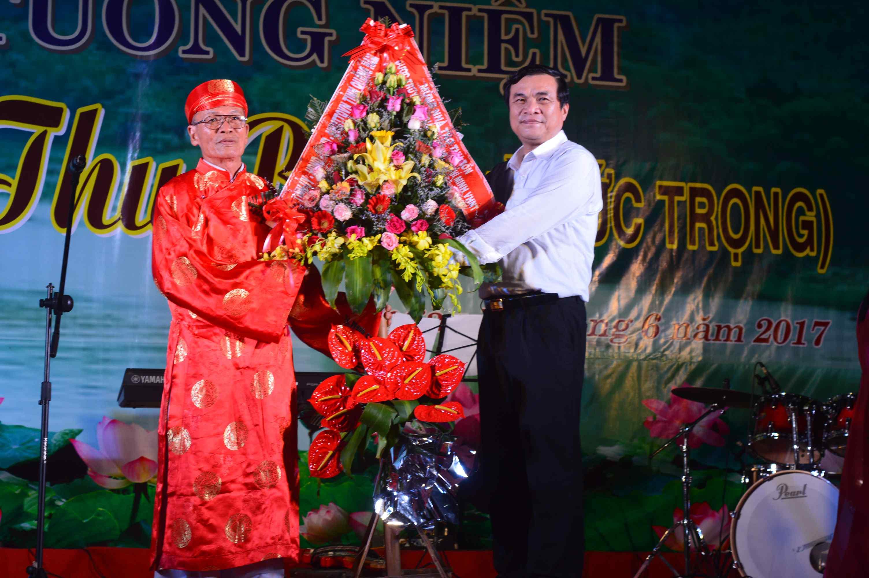 Lãnh đạo tỉnh tặng hoa chúc mừng gia tộc Hà Đức của nhà thơ Thu Bồn. Ảnh: Q.T