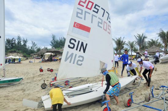 Các nhân viên hỗ trợ đưa thuyền buồm ra biển để hạ thủy.