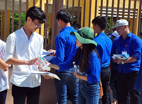 """Tình nguyện viên """"Tiếp sức mùa thi"""" phát nước uống miễn phí cho thí sinh tại điểm thi Trường THPT Trần Cao Vân. Ảnh: VINH ANH"""