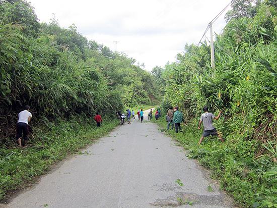 Đoàn viên thanh niên xã A Tiêng phát quang tuyến đường đảm bảo an toàn giao thông.  Ảnh: Bhơriu Quân