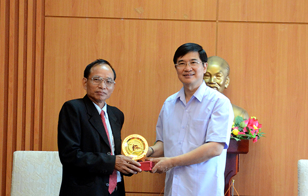 Secretary Quang (right) offers the symbol of Quang Nam's heritages to Chairman Khammay Duongcannha