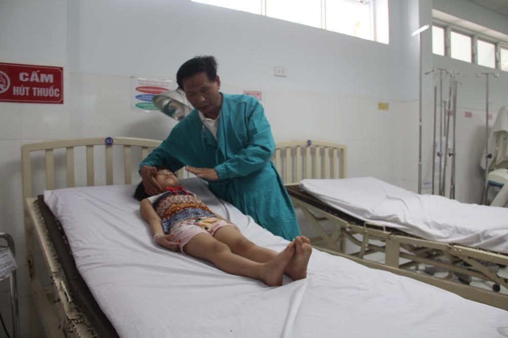 Bác sĩ Giám kiểm tra sức khỏe cháu bé khi đã gắp thành công đồng xu.