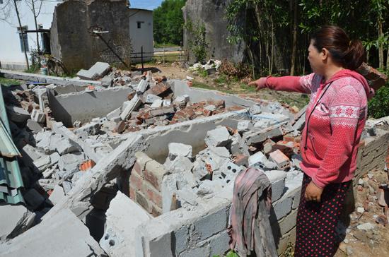 Bà Phan Thị Lan bên hiện trường đống gạch đá đổ vụn nằm ngổn ngang sau khi chính quyền địa phương cưỡng chế công trình ngày 10.7. Ảnh: T.N
